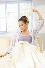 Young woman stretching in pyjama