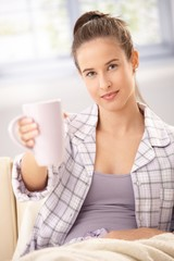 Woman in pyjama offering coffee