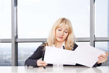 woman sitting at a table in the office and work with documents