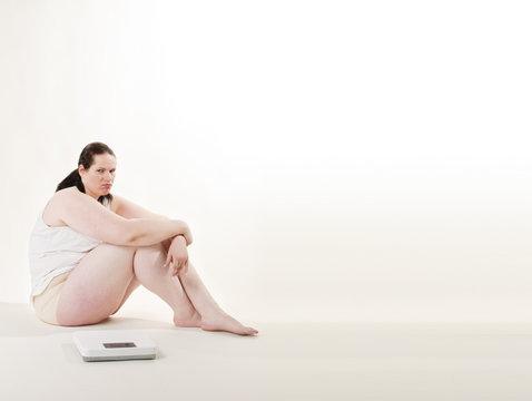 Übergewichtige erwachsene Frau auf der Waage