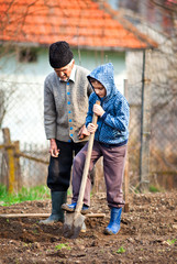 Senior farmer with grandson in the garden