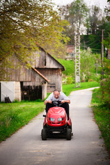 Cheerful gardener riding tractor mower on countryside road.