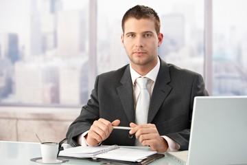 Elegant businessman sitting in bright office