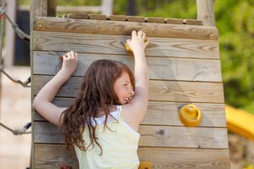 lachendes mädchen klettert auf dem spielplatz
