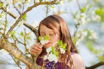 junges mädchen riecht an blüten