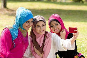 three muslim girls with cellphone