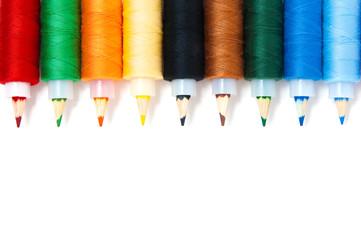 Colorful pencils inside thread reels