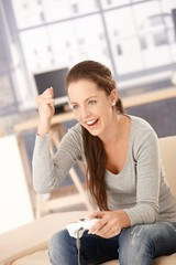 Attractive female playing video game at home