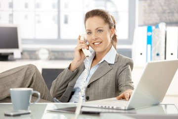 Attractive businesswoman talking on phone smiling