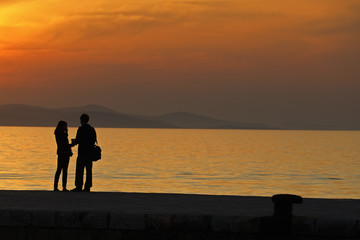 Young couple standing on a jetty at sunset