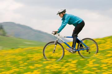Spring bike riding - woman downhill on bike in dandelion