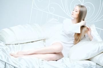 Girl combing her hair in bed