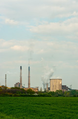 power plant with green grass and smoke rising