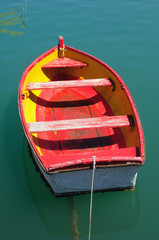 Old red fishing boat floating on the water