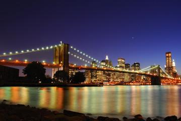 Tuinposter Brooklyn Bridge The Brooklyn Bridge illuminate at night with skyscrapers behind.