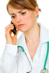 Worried medical female doctor talking on mobile phone