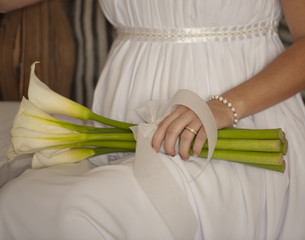 Bride holding flowers while sat down