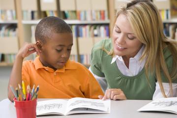 Kindergarten teacher helping student with reading skills