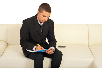 Business man writing and sitting sofa