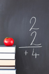Stack of books with a red apple and a blackboard with a simple f