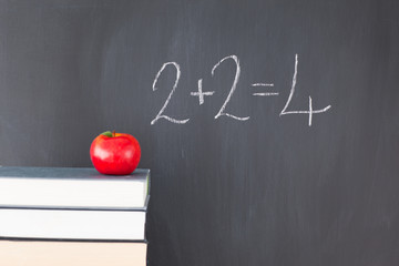 """Stack of books with a red apple and a  blackboard with """"2+2=4"""" w"""