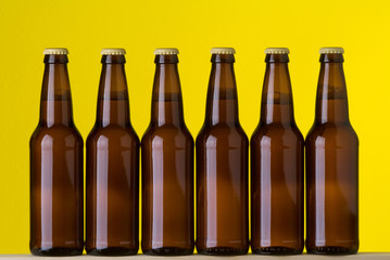 Bottles of Cold Beer on Yellow Background