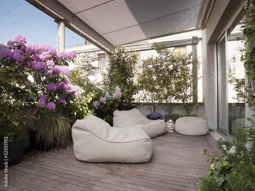 grande terrazzo con moderne poltrone e fiori\