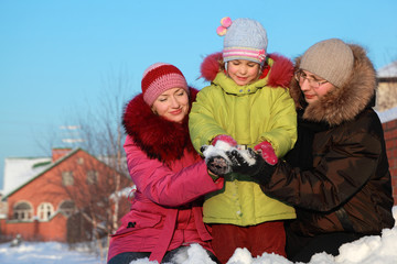father and mother offer to daughter to make snowball outdoors