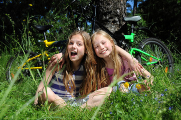 Little girls with cycles sitting on the green grass