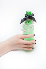 Hand holding a decorated green beer bottle