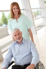 Nurse helping senior man in wheelchair