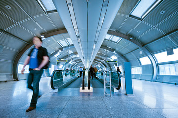futuristic indoor walkway with blurred commuters