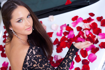 Young woman with New car in red rose petals