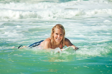 attractive woman bodyboards on surfboard