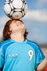 junger fußballer balanciert ball auf dem kopf
