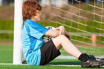 kleiner fußballspieler lehnt an torpfosten