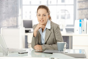 Young businesswoman sitting in bright office