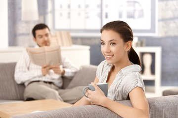 Young couple sitting on sofa at home smiling