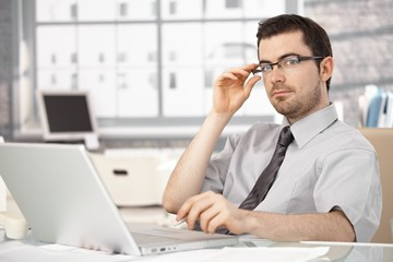 Young businessman sitting at desk using laptop
