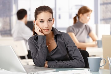 Young woman sitting at desk others working behind