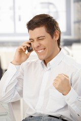 Happy businessman getting good news on phone