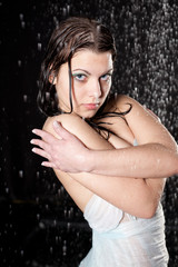 beautiful girl in the rain against a dark background