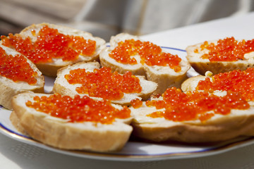 Red caviar sandwiches on plate.
