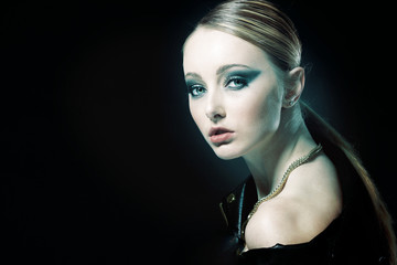 Young girl with blond hair posing on black background.