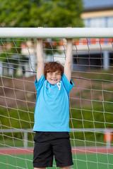 starker junge hängt am fußballtor