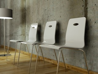 Weisse Stühle vor Betonwand