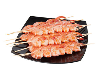 Skewers of shrimp on a black plate, isolated on a white