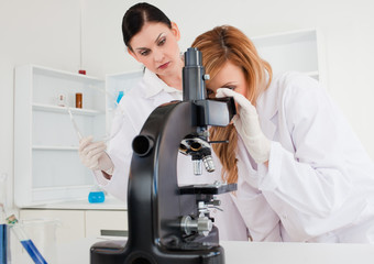 Cute female scientist looking through a microscope helped by her