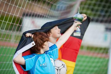 junge fußballer mit pokal und flagge