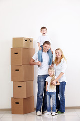 Happy family with boxes indoors
